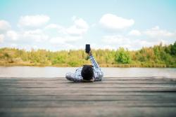Person liegend am See mit Smartphone in der Hand
